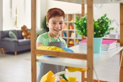 Adorable little boy in rubber gloves cleaning shelf with rag at home. Cute kid helping to do domestic chores