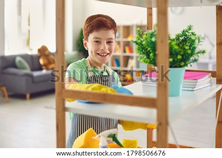 Adorable little boy in rubber gloves cleaning shelf with rag at home. Cute kid helping to do domestic chores Foto d'archivio ©