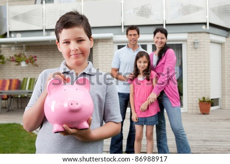 Adorable little boy inserting coin in a piggy bank with her family in background