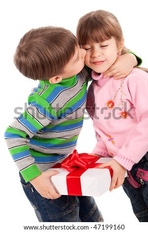 Adorable little boy kissing a girl holding gift box