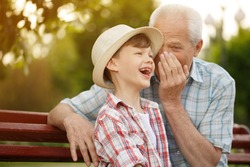 Adorable little boy laughing happily while his grandfather whispering something funny to his ear happiness emotions expressive together family childhood parenting communication interacting lifestyle