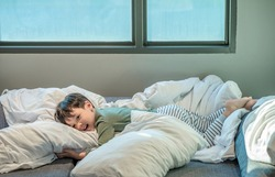 Adorable little boy lying in bed. people, children, rest and comfort concept. Soft focus. Copy space.