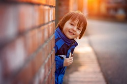 Adorable little boy, next to brick wall, eating chocolate bar on sunset, springtime