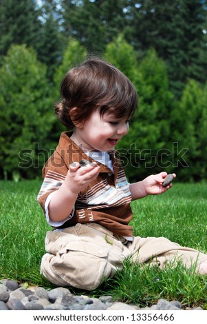 Adorable little boy playing in the grass outside on a hot summer day. Vertically framed shot.