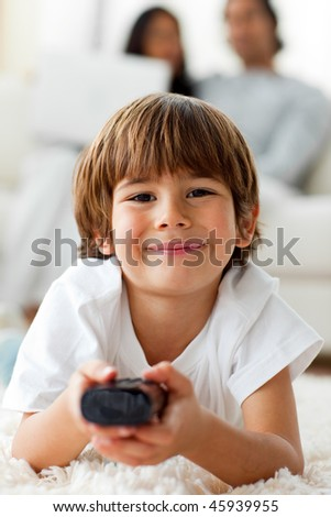 Adorable little boy watching TV lying on the floor in the living-room