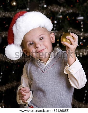 Adorable little boy wearing a Santa Hat in front of a Christmas tree