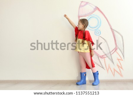 Adorable little child playing astronaut near wall with drawing of spaceship indoors Stock photo ©