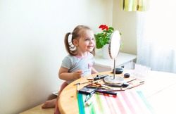 Adorable little child with dirty face playing with cosmetics and doing makeup while looking in mirror