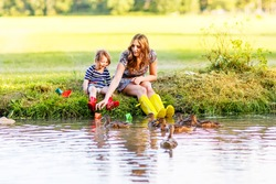 Adorable little girl and her mom playing with paper boats and feeding ducks in a river. Creative leisure with kids.