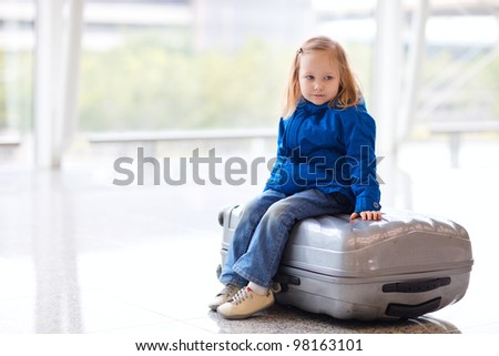 Adorable little girl at airport sitting on suitcase