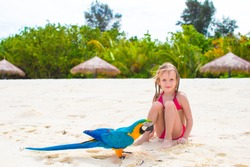 Adorable little girl at beach with colorful parrot