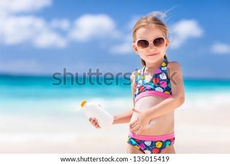 Adorable little girl at tropical beach applying sunblock cream