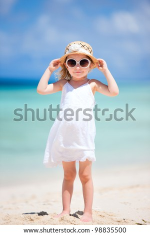 Adorable little girl at tropical white sand beach