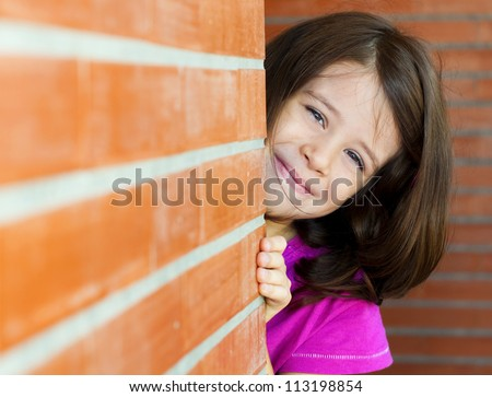 Adorable little girl behind a brick wall