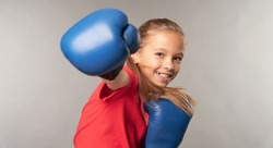 Adorable little girl boxer practicing punches in studio