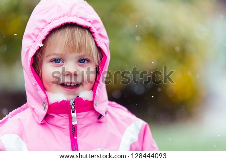 adorable little girl bundled up int the snow