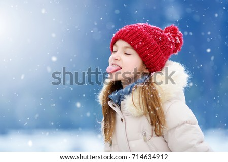 Adorable little girl catching snowflakes with her tongue in beautiful winter park. Cute child playing in a snow. Winter activities for kids.
