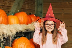 Adorable little girl choosing halloween pumpkin on farm market