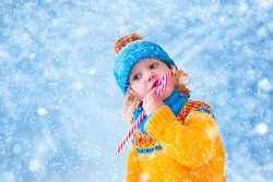 Adorable little girl, cute toddler in a blue knitted hat and yellow sweater, eating Christmas red sugar candy and playing with snow catching snowflakes having fun outdoors in a beautiful winter park