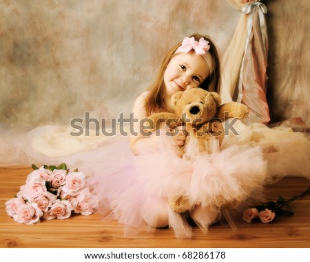 Stock Photo Adorable little girl dressed as a ballerina in a tutu, hugging a teddy bear next to pink roses.