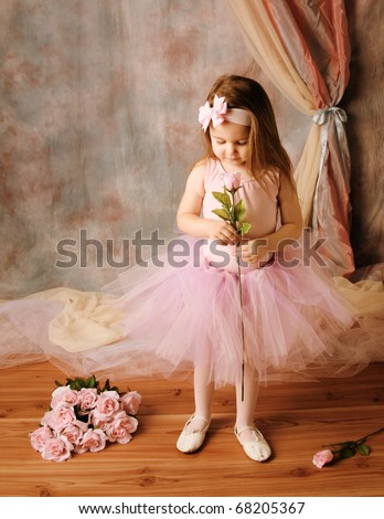 Adorable little girl dressed as a ballerina in a tutu standing next to pink roses.