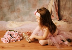 Adorable little girl dressed as a ballerina in a tutu, tying her ballet slippers