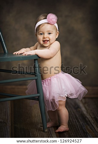 Adorable little girl dressed in a pink tutu and headband.