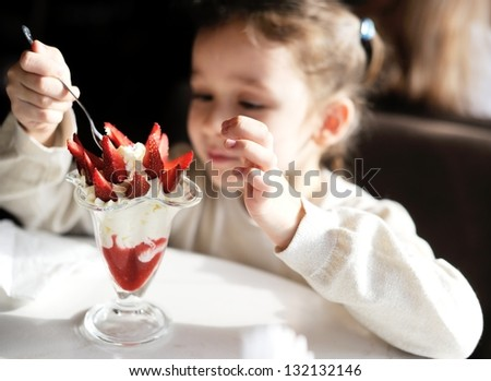 Adorable little girl eating ice cream at restaurant