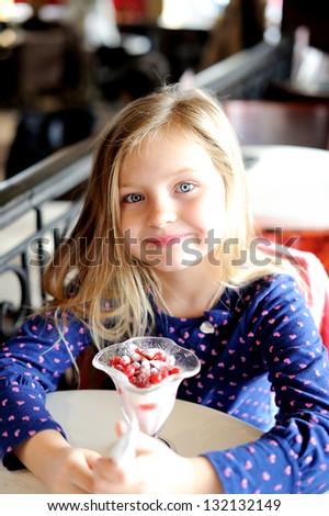 Adorable little girl eating ice cream at restaurant