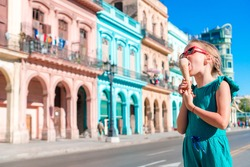 Adorable little girl eating ice-cream in popular area in Old Havana, Cuba. Portrait of cutiest kid outdoors on a street of Havana