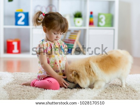 Adorable little girl feeding cute dog in her room #1028170510