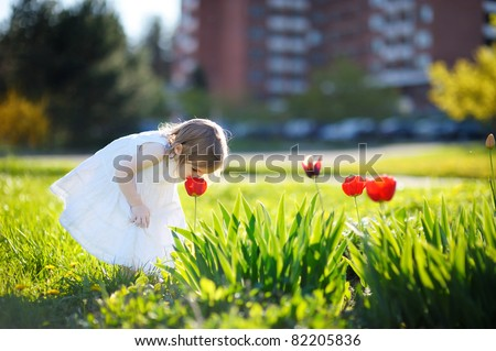 Adorable little girl girl smelling a tulip at summer