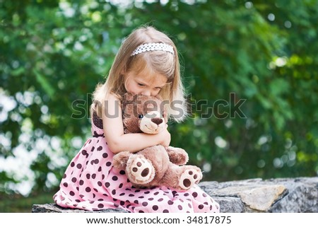 Adorable little girl giving her teddy bear a kiss on the head. Shallow DOF. - stock photo