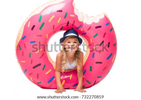 e44d0d6f895e3 adorable little girl having fun with swim ring and smiling at camera  isolated on white