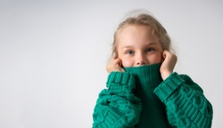 Adorable little girl hiding lower part of her face under thick collar of warm knitted sweater. Children, gesturing and emotions, happiness, winter. Close up studio shot isolated on white, copy space
