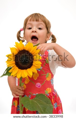 adorable little girl holding big yellow sunflower