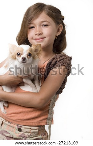 Adorable little girl holding chihuahua puppy standing and looking up