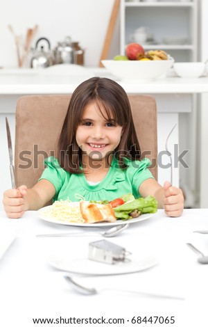 Adorable little girl holding forks to eat pasta and salad in the kitchen