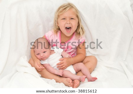 Adorable little girl holding her baby brother
