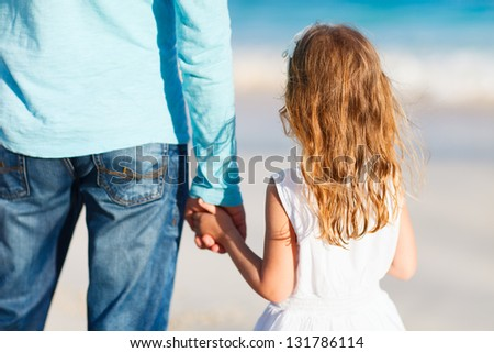 Adorable little girl holding her father hand - stock photo