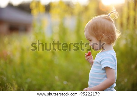 Adorable little girl in a meadow eating strawberry