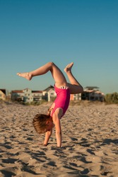 Adorable little girl in a pink leotard is engaged in gymnastics on a sandy beach