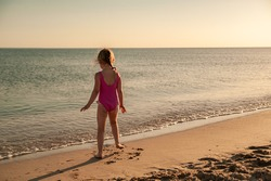 Adorable little girl in a pink leotard is engaged in gymnastics on the seashore