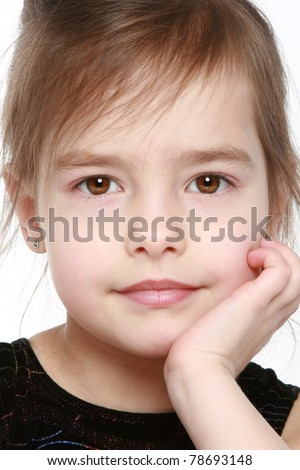 Adorable little girl in black dress. Close-up portrait on a white background