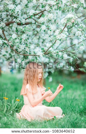 Adorable little girl in blooming apple garden on beautiful spring day #1083640652