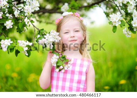 Adorable little girl in blooming apple tree garden on beautiful spring day #480466117