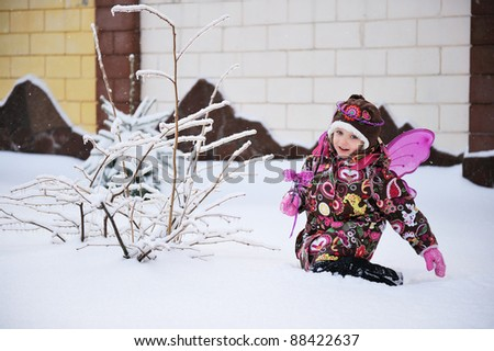 Adorable little girl in colorful snow suit with fairy wings and magic wand plays outdoors in snowfall