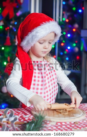 Adorable little girl in Santa hat  baking gingerbread Christmas cookies at home