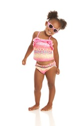 Adorable little girl in sunglasses and a bathing suit. Isolated on white.
