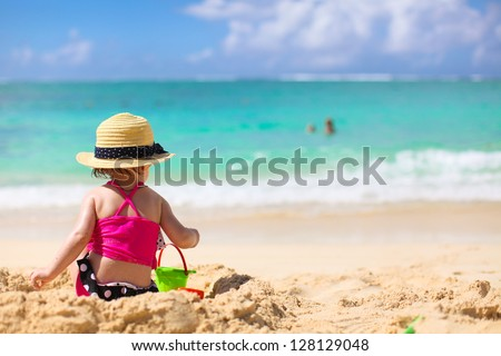Adorable little girl in swimsuit and hat at tropical beach